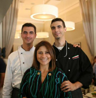 Fiorella Blanco standing between the Bearzi twin brothers smiling on the restaurant