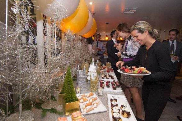 People enjoying a pastry buffet set up on a nicely decorated table with golden and whites ballons
