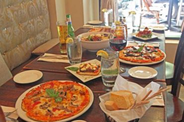 A table with pizza and salad plates on it