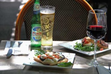 An outside table of the restaurant with two plates of bread entrees, a cup of wine and a bottle of beer